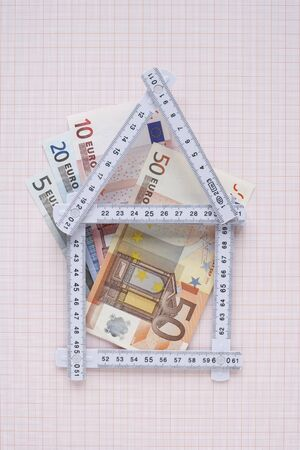 real estate sold: House Made of Expandable Ruler and Euros on Graph Paper