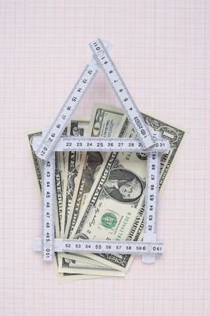 House Made of Expandable Ruler and American Currency on Graph Paper