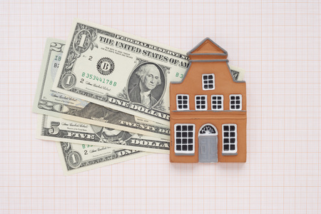 real estate sold: House and American Currency on Graph Paper