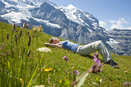 Woman Lying on Grass on Mountain Side, Bernese Oberland, Switzerland LANG_EVOIMAGES
