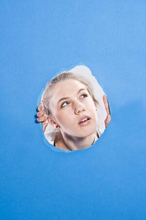 skepticism: Teenage Girl Looking Through Hole LANG_EVOIMAGES