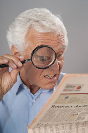 skepticism: Man Looking at Newspaper with Magnifying Glass