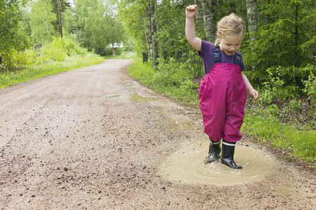 Young Girl Playing in Puddle, Sweden