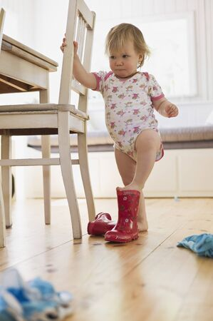 Girl Putting on Rubber Boots