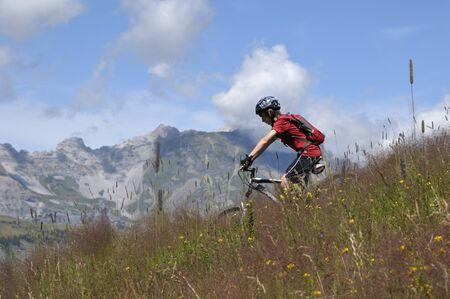 10 15 years: Boy Riding Bicycle in Mountains, Alps, France LANG_EVOIMAGES