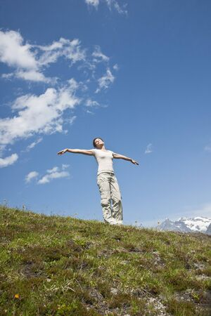Woman Standing on Mountain Side with Arms Outstretched, Bernese Oberland, Switzerland
