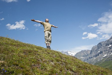 Man Standing on Mountain Side with Arms Outstretched, Bernese Oberland, Switzerland