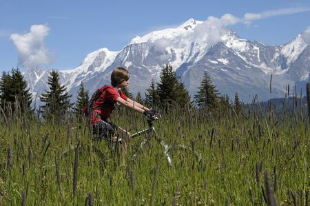 Boy Riding Bicycle in Mountains, Alps, France LANG_EVOIMAGES
