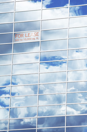 real estate sold: Sky and Clouds Reflected in Building Windows with For Lease Sign