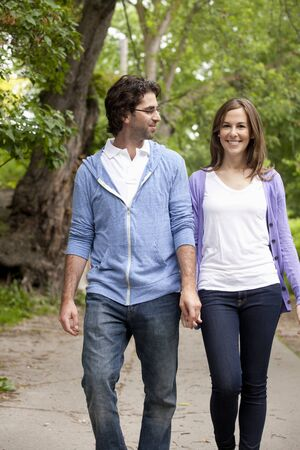 public offering: Young Couple Walking through Park
