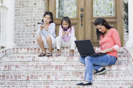 flip flops: Mother using Laptop and Daughters using Handheld Video Games