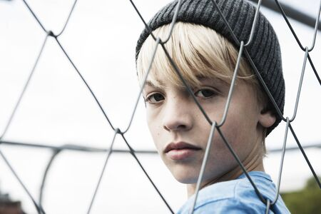 glower: Portrait of Boy Looking Through Chain Link Fence,Mannheim,Baden-Wurttemberg,Germany