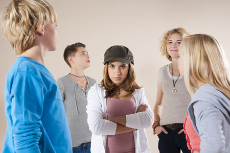 10 15 years: Portrait of Teenage Girl wearing Baseball Hat Looking at Camera,Standing in the Middle of Group of Teenage Boys and Grils,Studio Shot on White Background