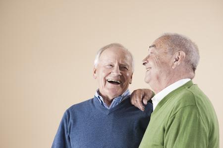 socialise: Portrait of Two Senior Men Laughing Together,Studio Shot on Beige Background LANG_EVOIMAGES