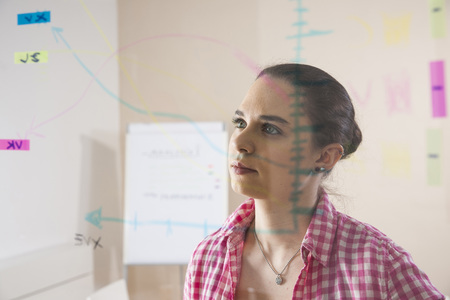 figuring: Young Businesswoman Working in Office Looking at Plans Displayed on a Glass Board LANG_EVOIMAGES