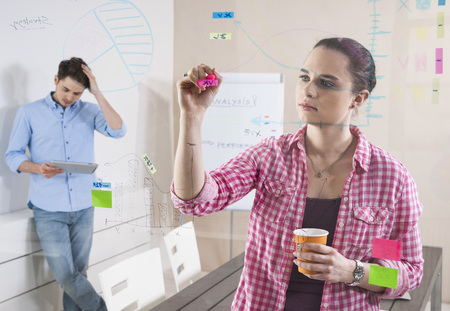 Young Man and Young Woman Working in an Office,Looking Through Glass Board,Germany LANG_EVOIMAGES
