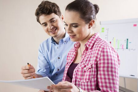 Young Businessman and Young Businesswoman Reading Document in Office LANG_EVOIMAGES