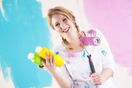 comparable: Studio Shot of Young Woman Holding Paint Roller,Deciding Between Paint Colours
