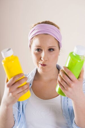 yellowish green: Studio Shot of Young Woman Holding Containers of Paint