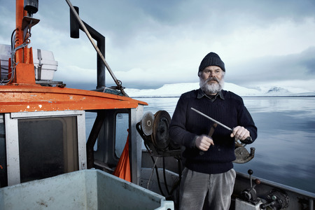 glower: Fisherman with gray beard,standing on small boat sharpening a knife on a winter day,Iceland