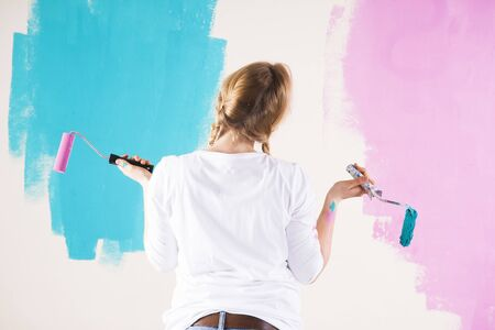 comparable: Studio Shot of Young Woman Holding Paint Rollers,Deciding Between Paint Colours