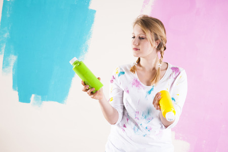 comparable: Studio Shot of Young Woman Holding Paint Cotainers,Deciding Between Paint Colours