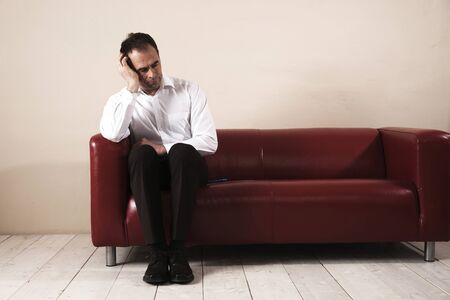 Mature Man Sitting on Sofa and Waiting LANG_EVOIMAGES