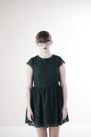 Portrait of Young Woman wearing Green,Lace Dress and Horn-rimmed Eyeglasses,Looking at Camera,Studio Shot on White Background