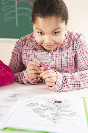 Portrait of Girl Looking at Flower in Classroom,Baden-Wurttemberg,Germany LANG_EVOIMAGES