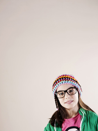 Portrait of Girl wearing Woolen Hat and Horn-rimmed Eyeglasses,Smiling at Camera,Studio Shot