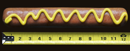 comparable: Hotdog with mustard beside measuring tape LANG_EVOIMAGES