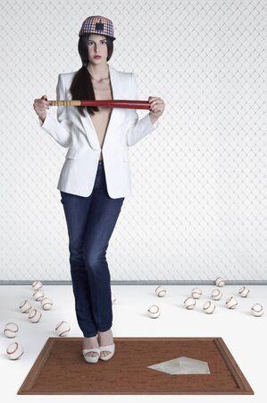 Portrait of young woman holding baseball bat,studio shot on white background