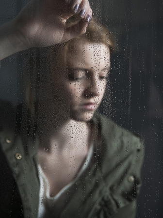 Portrait of teenage girl leaning against window,wet with raindrops LANG_EVOIMAGES