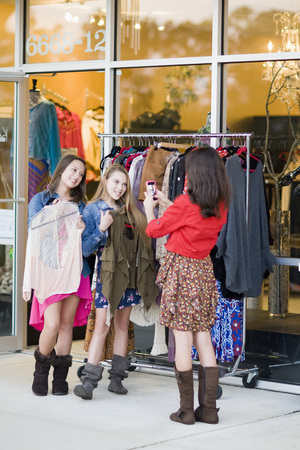 10 15 years: Pre-teen girls shopping for clothes and taking picture with smartphone