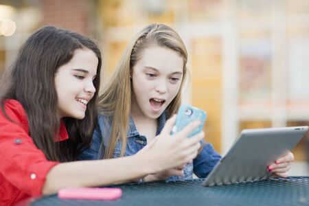 10 15 years: Pre-teen girls looking at cell phone and tablet computer,outdoors LANG_EVOIMAGES