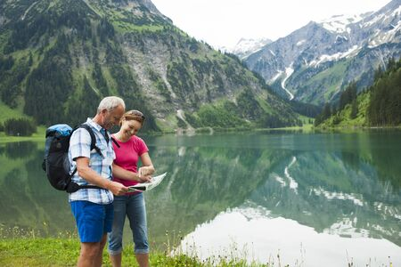 Mature couple looking at map,hiking in mountains,Lake Vilsalpsee,Tannheim Valley,Austria