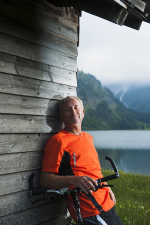 Mature Man leaning against Wooden Building with Mountain Bike,Vilsalpsee,Tannheim Valley,Tyrol,Austria