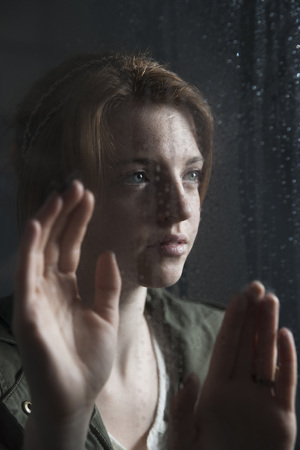 Teenage girl looking out with hands on window,wet with raindrops LANG_EVOIMAGES