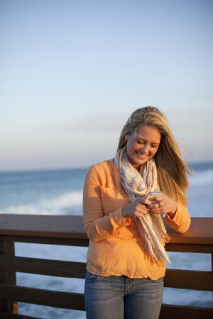 leaned: Young Woman Standing on Pier at Beach,Texting on Cell Phone,Jupiter,Palm Beach County,Florida,USA