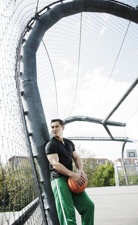 leaned: Mature man standing on outdoor outdoor basketball court,Germany