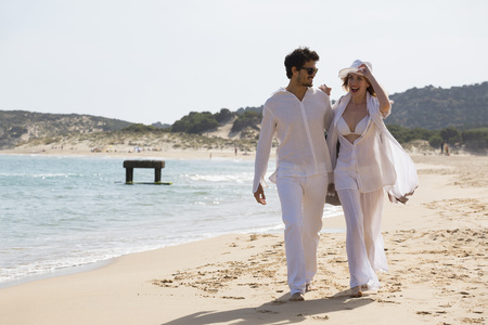 Young couple walking at the beach during summer holidays,Sardinia,Italy LANG_EVOIMAGES