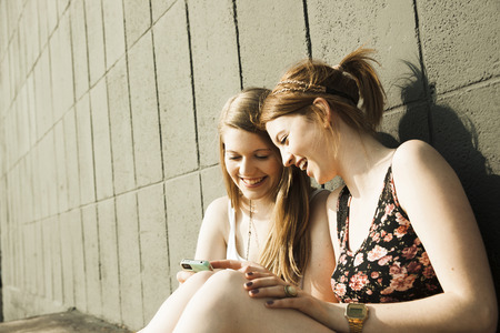 leaned: Young women sitting and leaning against wall,looking at smart phone together