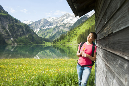 leaned: Mature Woman Standing by Wooden Building,Vilsalpsee,Tannheim Valley,Tyrol,Austria LANG_EVOIMAGES