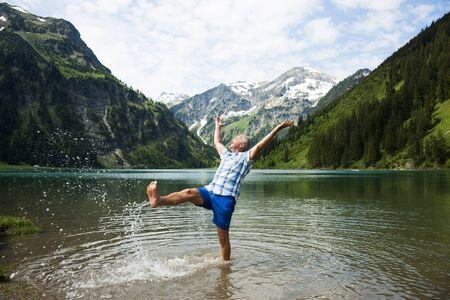 rejuvenated: Mature man standing in lake,kicking water,Lake Vilsalpsee,Tannheim Valley,Austria LANG_EVOIMAGES