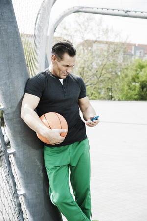 leaned: Mature man standing on outdoor basketball court looking at MP3 player,Germany LANG_EVOIMAGES