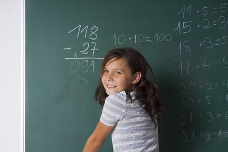 Girl standing in classroom in front of blackboard dong mathematical questions,Germany