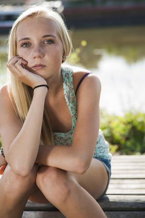 glower: Portrait of teenage girl outdoors,looking at camera,Germany