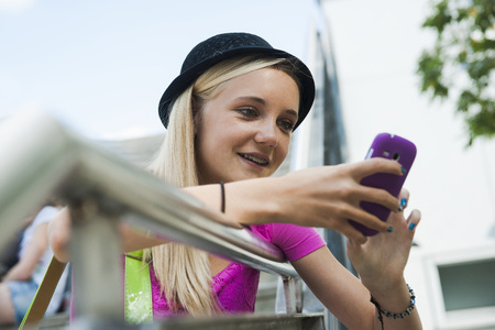 leaned: Teenage Girl using Cell Phone Outdoors,Mannheim,Baden-Wurttemberg,Germany LANG_EVOIMAGES