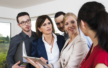 conferring: Group of young business people and businesswoman in discussion in office, Germany