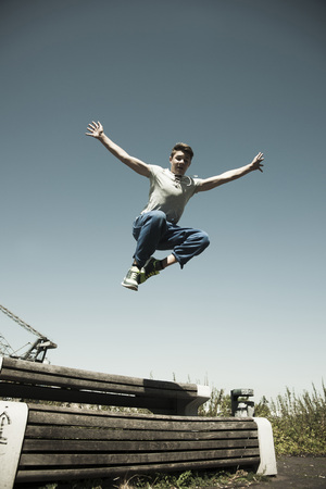 Low angel view of teenaged boy jumping over barrier,freerunning,Germany LANG_EVOIMAGES